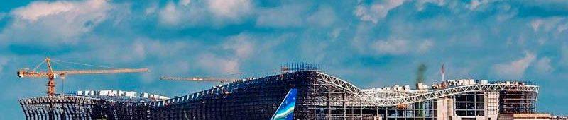 Строящийся новый терминал за самолетом на взлете